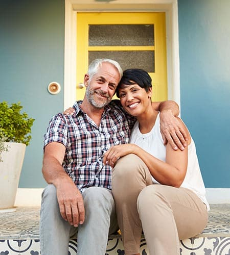Happy Couple on Their Front Porch - Tax Solutions - Tax Help