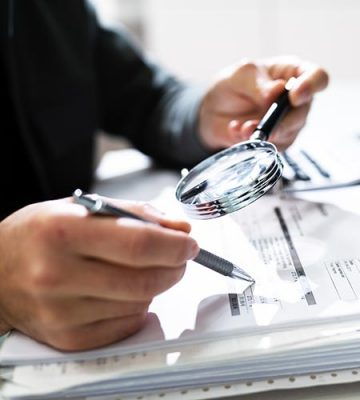 IRS Auditor Examining Records with a Magnifying Glass